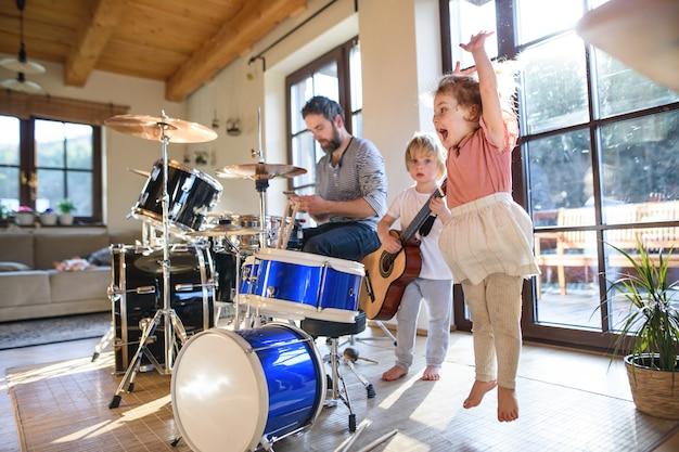 Retrato de crianças pequenas felizes com o pai dentro de casa em casa, tocando bateria.
