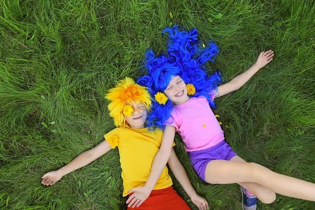 Retrato de crianças sorridentes com cabelo azul e amarelo, deitado na grama verde e acenando com as mãos de prazer com pétalas amarelas de flores no verão.