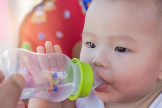 Retrato, de, cute, bebê, ligado, carro brinquedo, água potável, de, garrafa