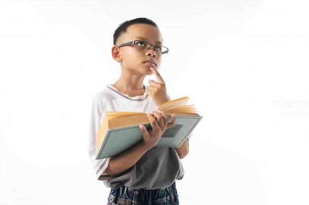 Retrato, de, cute, menino asian, estudante, pensando, e, segurando, livro grande, isolado, branco, fundo