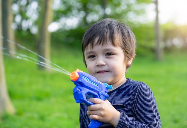 Retrato, de, cute, menino, jogando pistola água, parque