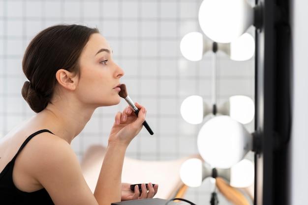 Retrato de dançarina elegante fazendo sua maquiagem