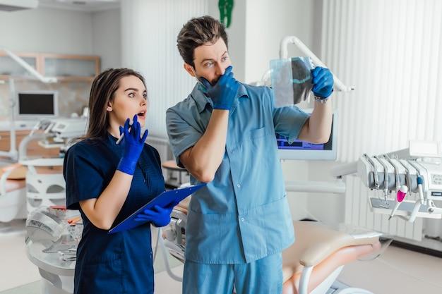 Retrato de dentista bonito em pé com seu colega e segurando o raio-x.
