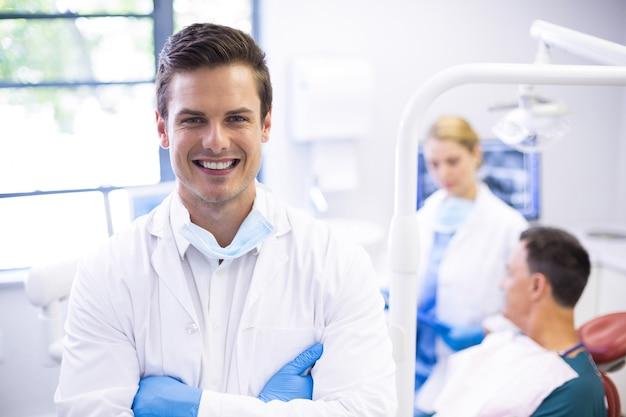 Retrato de dentista em pé com os braços cruzados