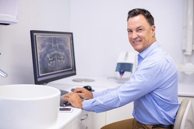 Retrato de dentista feliz examinando relatório de raio-x no computador