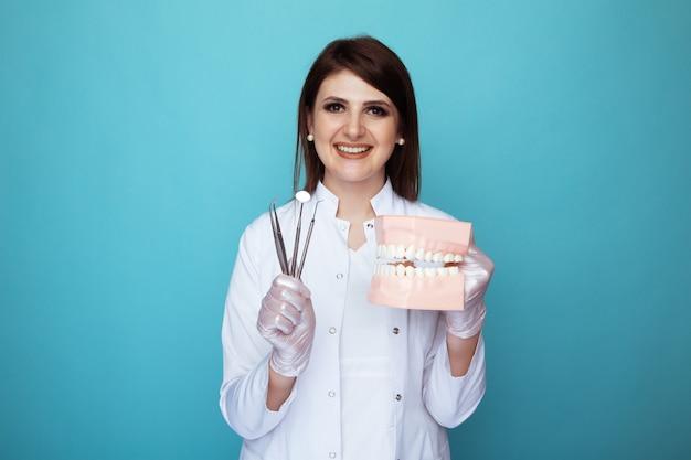 Retrato de dentista feminino segurando material médico e mandíbula falsa isolada.