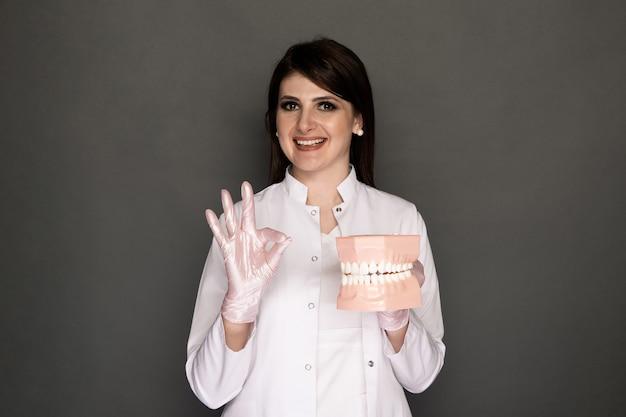 Retrato de dentista feminino segurando o material odontológico isolado.