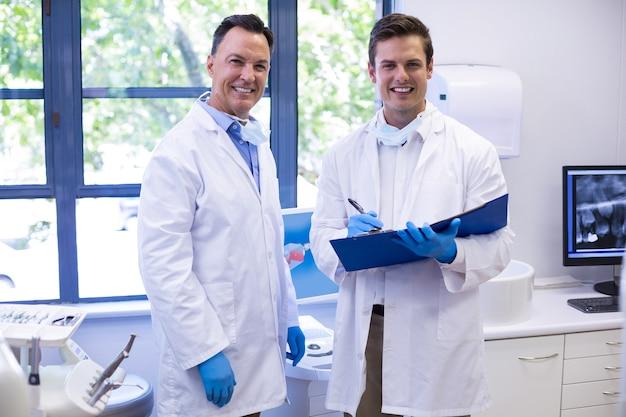 Retrato de dentistas felizes em pé com uma pasta