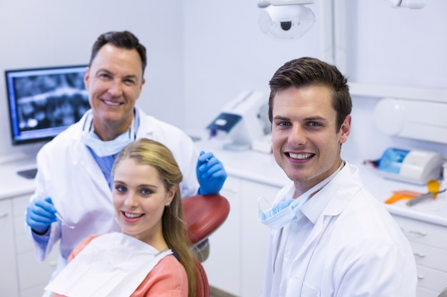 Retrato de dentistas sorridentes e paciente do sexo feminino