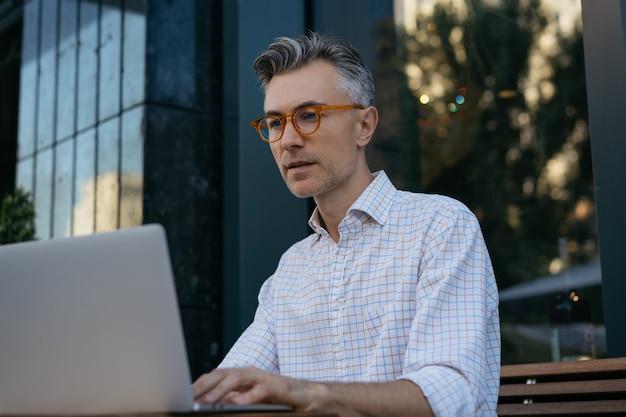 Retrato de desenvolvedor sênior usando laptop, trabalhando ao ar livre