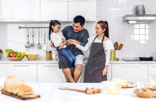 Retrato de desfrutar de amor feliz pai e mãe de família asiática com filha pequena menina asiática se divertindo cozinhando junto com assar biscoitos e ingredientes do bolo na mesa da cozinha
