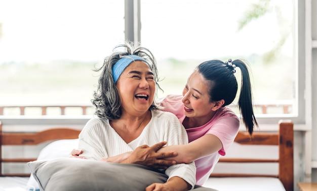 Retrato de desfrutar feliz amor família asiática sênior madura mãe e filha sorrindo, rindo, abraçando e se divertindo juntos em bons momentos em casa