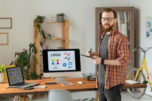 Retrato de designer de marca freelance confiante com barba desenhando na mesa do digitalizador no escritório doméstico