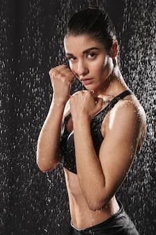 Retrato de desportista bastante concentrado, fazendo exercícios de kickboxing e olhando para a câmera posando sob chuva, isolada sobre fundo preto