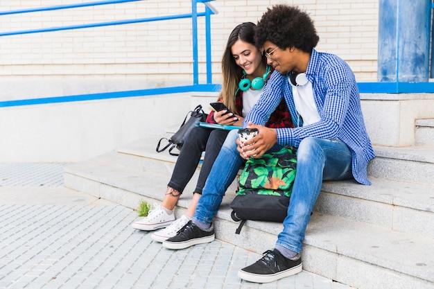 Retrato, de, diverso, adolescente, macho fêmea, estudantes, sentando, ligado, a, passos, usando, telefone móvel