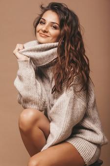 Retrato de doce doce bonito mulher morena sorridente. garota de suéter cinza casual. modelo posando no estúdio. sentado na cadeira