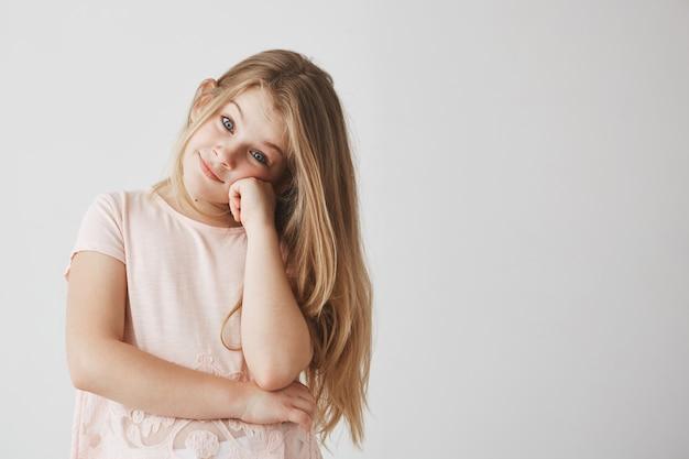 Retrato de doce menina pequena com cabelo comprido leve, vestido com camiseta rosa com olhar alegre, segurando a cabeça com a mão.