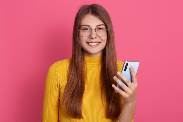 Retrato de doce sincero adorável jovem fêmea atraente tendo sorriso agradável, segurando o smartphone, estar de bom humor, em pé isolado sobre parede rosa. conceito de pessoas e tecnologia.
