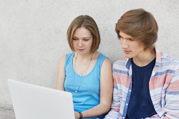 Retrato de dois adolescentes sentados juntos, olhando seriamente para laptop, lendo o livro on-line. na moda adolescente e sua namorada