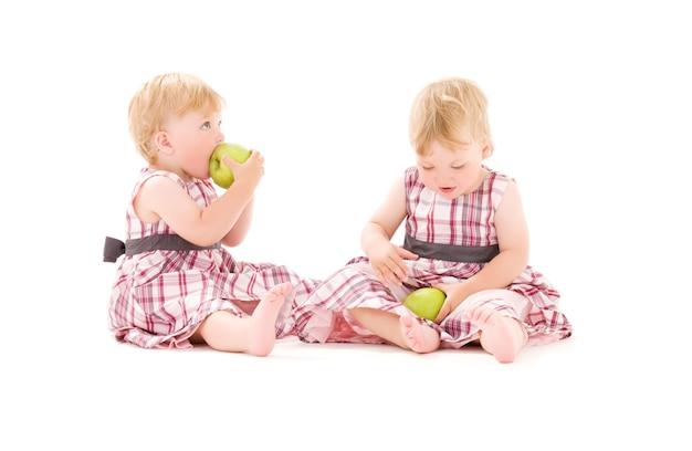 Retrato de dois adoráveis gêmeos sobre uma parede branca
