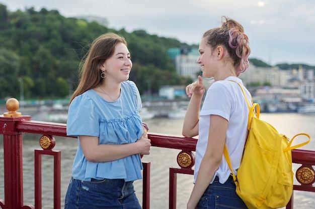 Retrato de dois amigos adolescentes andando e conversando na ponte pedonal num dia ensolarado de verão. amizade, estilo de vida, juventude, adolescentes