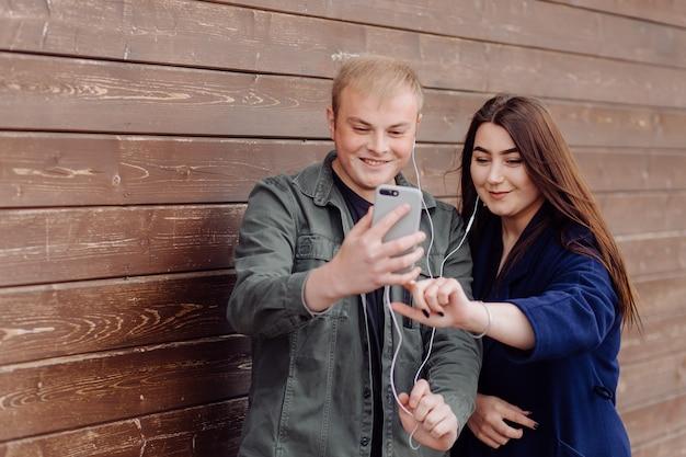 Retrato de dois amigos usando celular e ouvindo música na rua