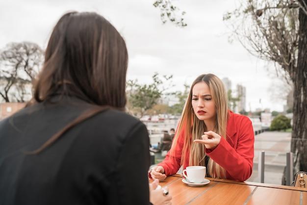Retrato de dois amigos zangados, conversando séria e discutindo enquanto está sentado em uma cafeteria
