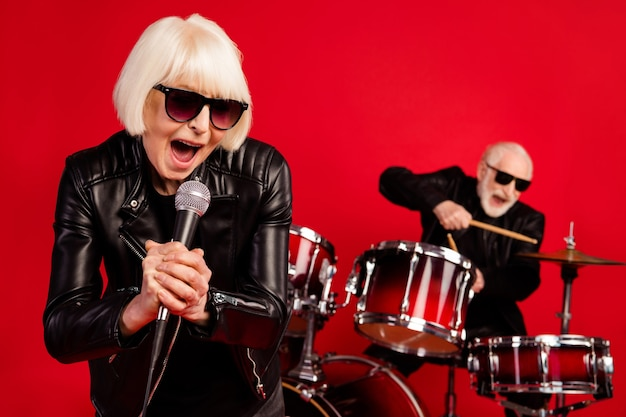 Retrato de dois aposentados aposentados aposentados mulher cantar composição solo homem tocar tambor baqueta desfrutar de lazer clube noturno evento vestir couro isolado sobre fundo de cor de brilho brilhante