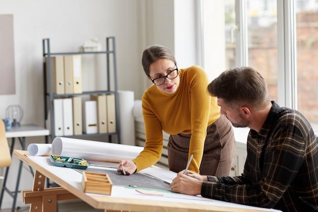 Retrato de dois arquitetos apontando para a planta baixa enquanto trabalhava em plantas no local de trabalho,