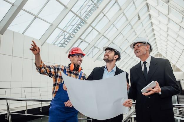 Retrato de dois arquitetos e capatazes de sucesso discutindo o design do projeto