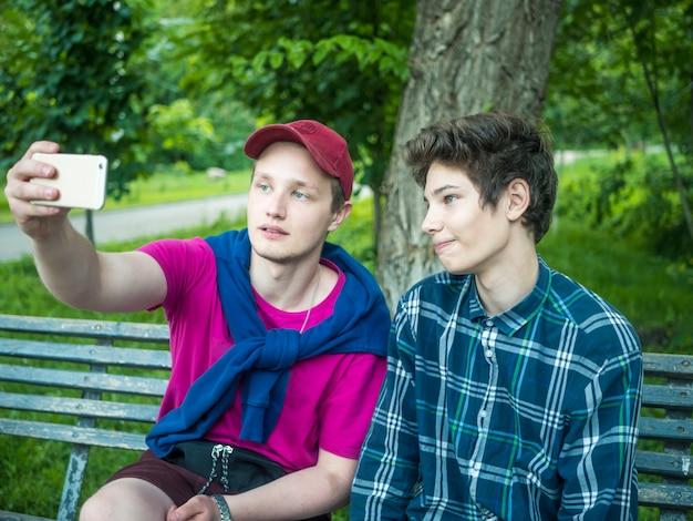 Retrato, de, dois, atraente, irmãos jovens, fazendo, um, retrato auto, usando, um, telefone, ao ar livre