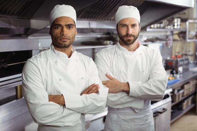 Retrato de dois chefs de pé juntos com os braços cruzados em uma cozinha comercial