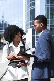 Retrato, de, dois, colega africana, ficar, frente, predios, falando, um ao outro