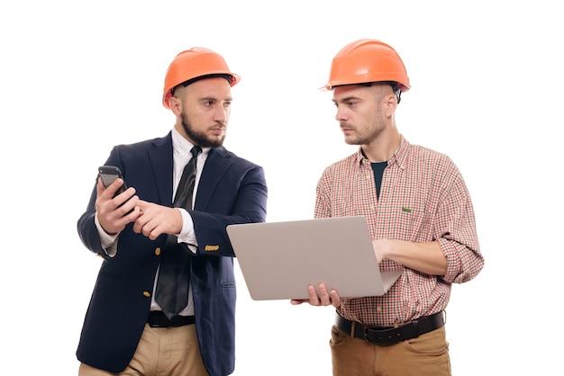 Retrato de dois construtores em capacetes laranja protetores em pé sobre um fundo branco isolado e olhando para o visor do laptop. discutir projeto de construção Foto Premium