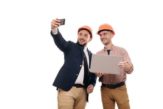 Retrato de dois construtores em capacetes laranja protetores em pé sobre um fundo branco isolado e olhando para o visor do laptop. discutir projeto de construção