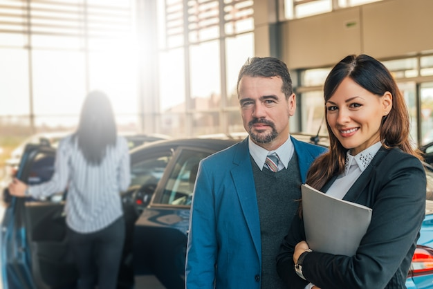 Retrato de dois consultores felizes das vendas do carro que trabalham dentro da sala de exposições do veículo.