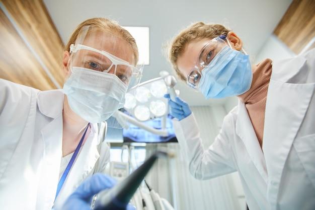 Retrato de dois dentistas com máscaras protetoras e óculos, olhando para a frente enquanto trabalhava com instrumentos médicos em equipe