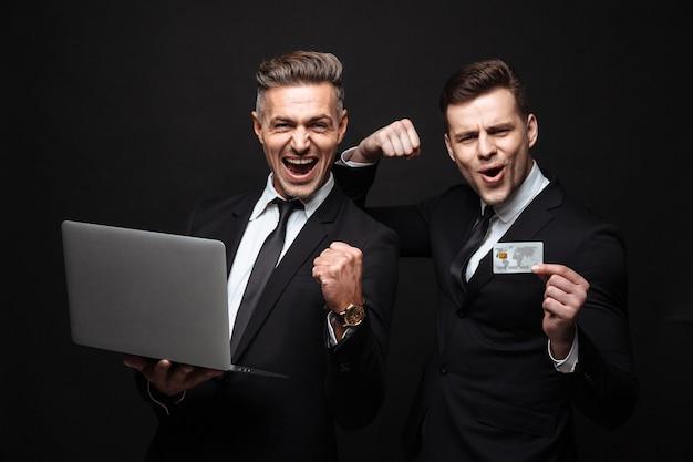 Retrato de dois empresários alegres vestidos com um terno formal celebrando enquanto seguram o laptop e o cartão de crédito isolados sobre a parede preta