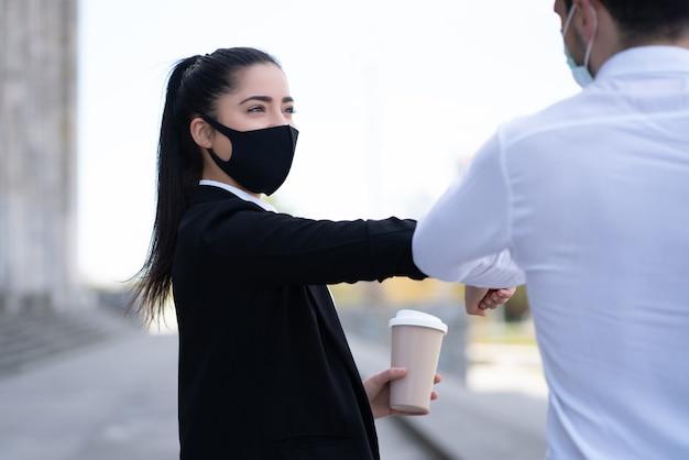 Retrato de dois empresários batendo os cotovelos para cumprimentar um ao outro ao ar livre.