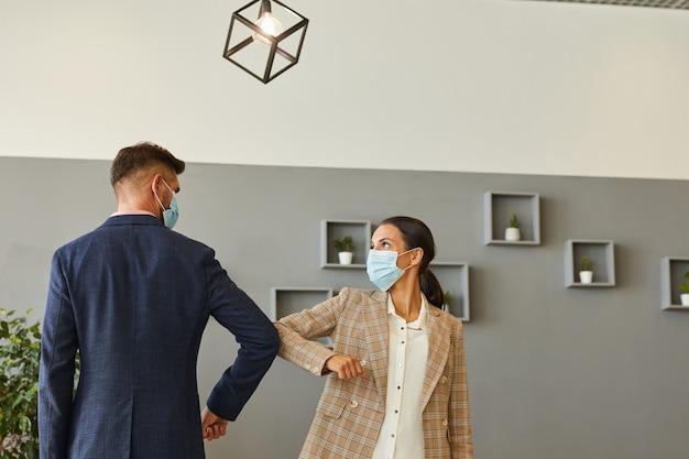 Retrato de dois empresários de sucesso usando máscaras e batendo os cotovelos na cintura como saudação sem contato em escritório pós-pandêmico, copie o espaço