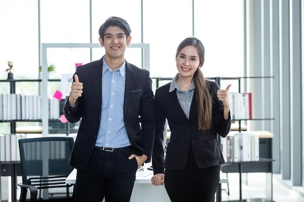 Retrato de dois empresários e parceiros de negócios discutindo negócios adultos positivos mostrando os polegares para cima e ideias em uma reunião no escritório.