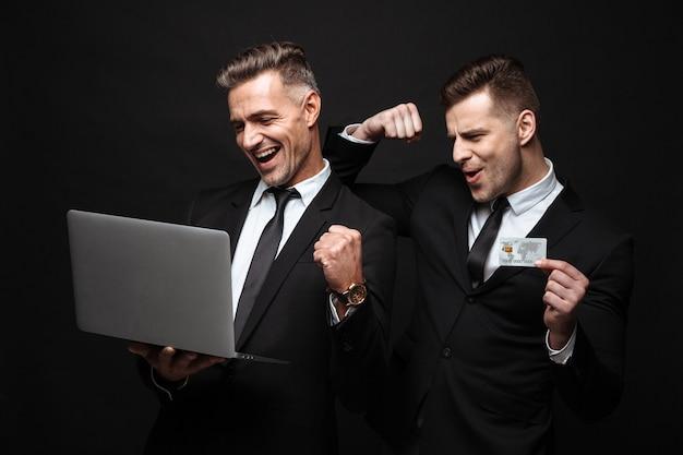 Retrato de dois empresários felizes, vestidos com um terno formal, comemorando enquanto seguram o laptop e o cartão de crédito isolados sobre a parede preta