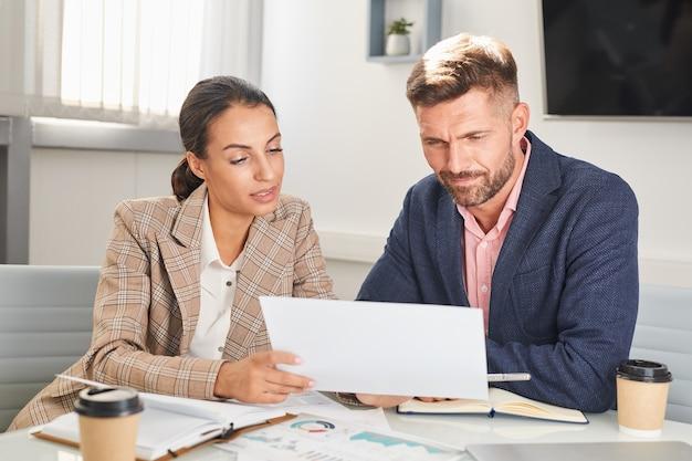 Retrato de dois empresários, homem e mulher, olhando documentos durante uma reunião no escritório