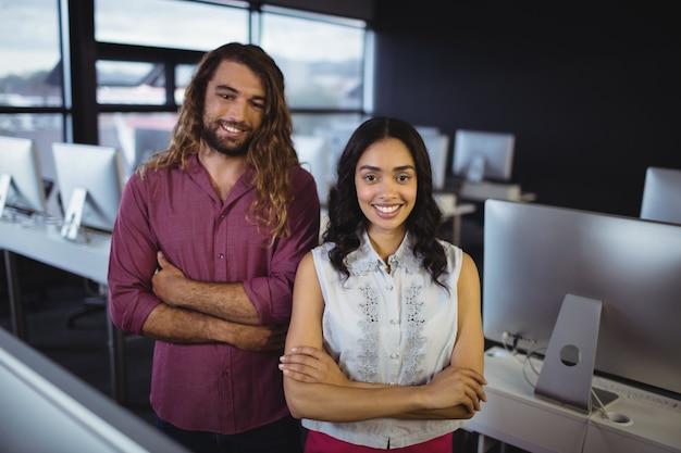 Retrato de dois engenheiros de som em pé com os braços cruzados