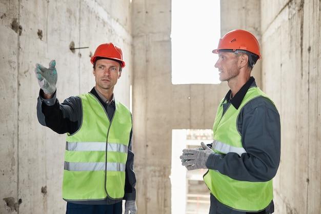 Retrato de dois engenheiros no canteiro de obras apontando para a cintura