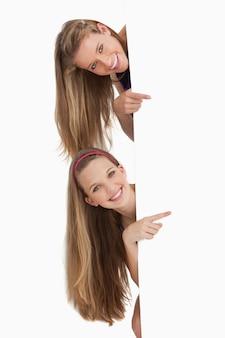 Retrato de dois estudantes de cabelo longo apontando para trás um sinal em branco