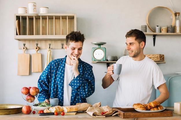 Retrato, de, dois, feliz, homem jovem, preparando café da manhã, em, cozinha