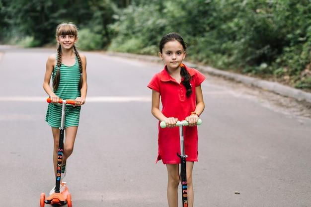 Retrato, de, dois, femininas, amigos, ligado, empurre scooter
