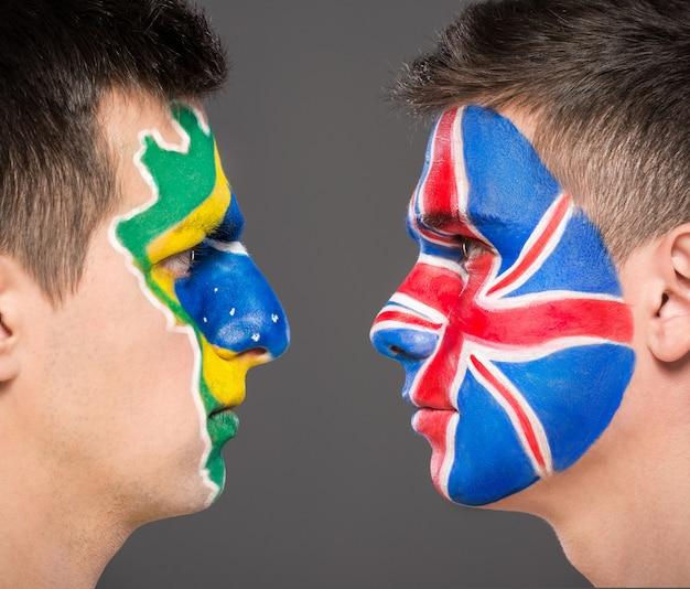 Retrato de dois homens com bandeiras pintadas em seus rostos.