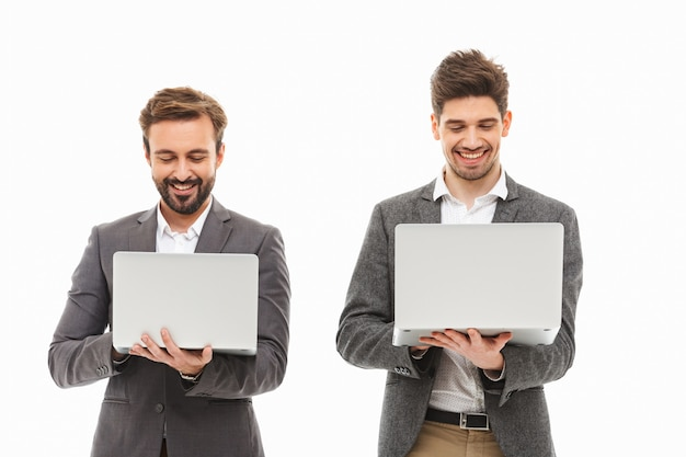 Retrato de dois homens de negócios animados usando um laptop